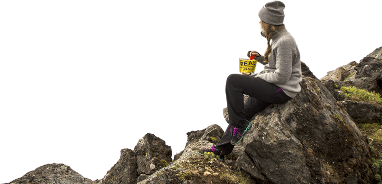 Person eating on a rock